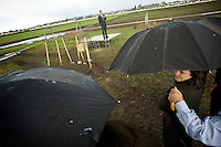 JEROME A. POLLOS/Press..Mandy Surratt takes cover under an umbrella during Tuesday's groundbreaking ceremony for West Ridge Elementary in Post Falls. Students and other attendees took shelter inside a school bus as a hail storm postponed the ceremony.