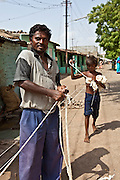 A young boy helps his father to make rope. They receive 7 rupees per Kilo of rope produced. The Shaishav Trust is trying to provide education and support for children in child labour.