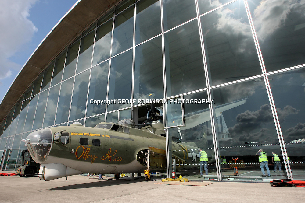 THE B-17 FLYING FORTRESS BEING SLOWING MOVED OUT OF ITS HANGER THROUGH A FIRE ESCAPE AT DUXFORD WAR MUSEUM ON THURSDAY MAY 19 WITH ONLY MILLIMETRES TO SPARE ON EITHER SIDE.THE PALNE WAS BEING MOVED FOR CONSERVATION WORK...It took a team of men nearly THREE HOURS to squeeze a huge Second World War US bomber plane through a narrow fire exit today (Thurs) - with just millimetres to spare...The B-17 Flying Fortress Mary Alice, which has a wing span of 104ft, was guided carefully through the tiny 9ft 4 fire door at the Imperial War Museum in Duxford, Cambs...Experts looked on nervously as the impressive flying machine was edged forwards inch by inch as it left the museum for £80,000 worth of conservation work...The plane has been housed in the American Air Museum, but is now suffering from corrosion and needs a new coat of paint...It was too expensive to remove the large glass wall from the side of the museum, so instead a team has spent TWO MONTHS dismantling the plane so it could fit through the small door..