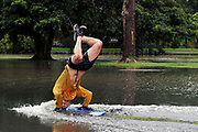 James Kean uses boogie boards to 'surf' a flooded park near the Cooks River in Sydney, Australia.