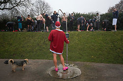 © Licensed to London News Pictures. 25/12/2017. London, UK. A man in a Santa suit shows before Members of the Serpentine Swimming Club brave the cold waters at the Serpentine Lake in Hyde Park, London to compete for the traditional Peter Pan Cup on Christmas Day, December 25, 2017. Photo credit: Ben Cawthra/LNP