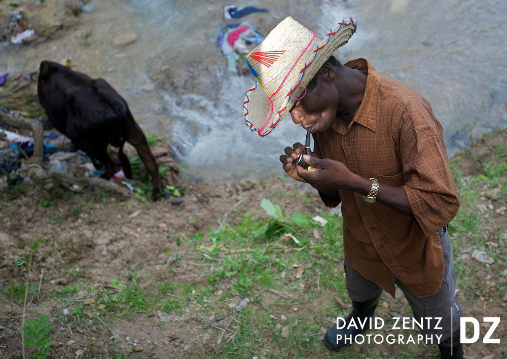 A rural farmer lights his pipe while standing near a cow that was brought for sacrifice to the Saut D'eau voodoo festival, a pilgrimage held beneath the waterfall in Saut D'eau, Haiti every July.