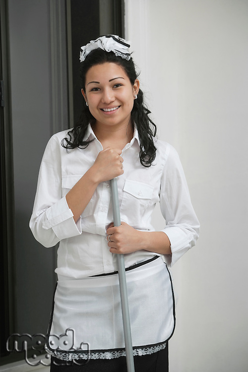 Portrait of young housemaid holding mop