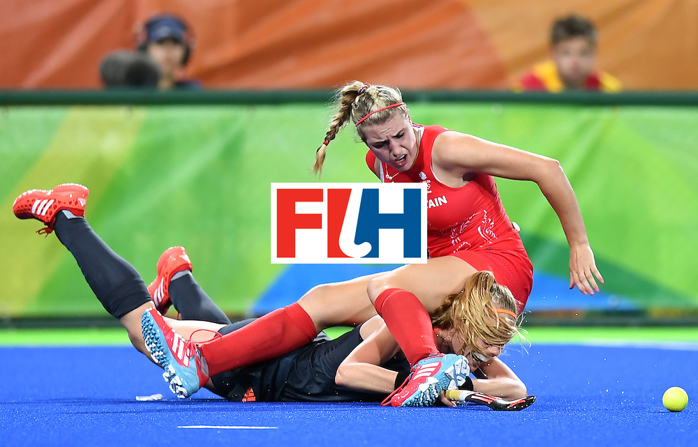 TOPSHOT - Britain's Lily Owsley (R) falls over Netherlands' Caia van Maasakker during the women's Gold medal hockey Netherlands vs Britain match of the Rio 2016 Olympics Games at the Olympic Hockey Centre in Rio de Janeiro on August 19, 2016. / AFP / MANAN VATSYAYANA        (Photo credit should read MANAN VATSYAYANA/AFP/Getty Images)