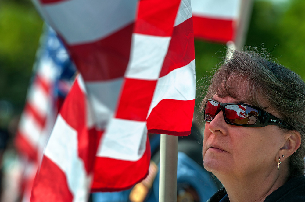 em052917h/a/Kelley Saiz, from Santa Fe and with the American Legion Riders, holds a flag during the Memorial Day ceremony at the Santa Fe National Cemetery on Memorial Day, Monday May 29, 2017. The keynote speaker at the event was Alan Martinez, deputy secretary of the N.M. Dept. of Veterans Services. (Eddie Moore/Albuquerque Journal