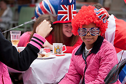 © Licensed to London News Pictures. 02/06/12. LONDON, UK. A young girl poses wearing Jubilee related clothing as she sits at a table in Ravenscroft Road in Canning Town, East London, during a Jubilee street party held by local residents. The Royal Jubilee celebrations. Great Britain is celebrating the 60th  anniversary of the countries Monarch HRH Queen Elizabeth II accession to the throne this weekend Photo credit : LNP