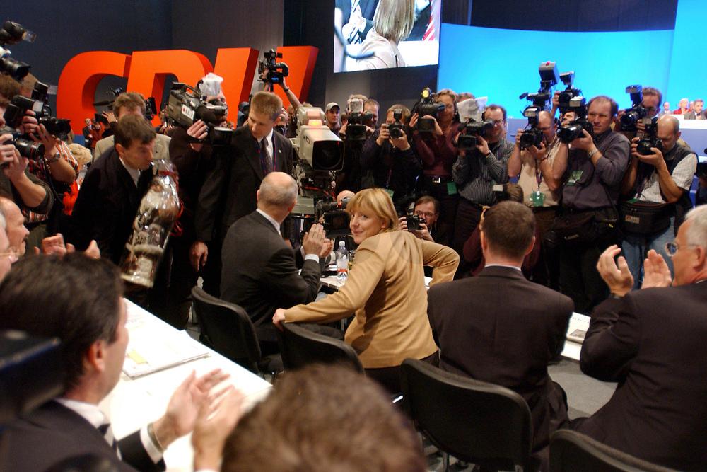 11 NOV 2002, HANNOVER/GERMANY:<br /> Angela Merkel, CDU Bundesvorsitzende, nimmt nach ihrer Wiederwahl den Applaus der Delegierten entgegen, CDU Bundesparteitag, Hannover Messe<br /> IMAGE: 20021111-01-112<br /> KEYWORDS: Parteitag, party congress, Jubel, Fotografen, Fotojournalisten, photographer, Kamera, Camera
