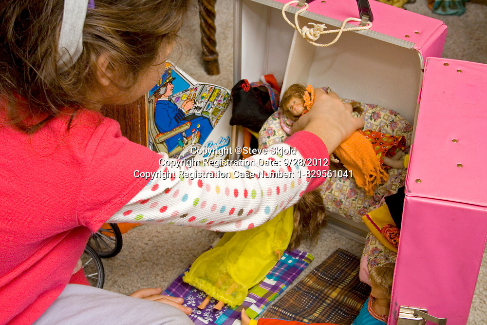 Young girl age 7 playing with her Barbie dolls in a pink suitcase storage container. Chicago Illinois IL USA
