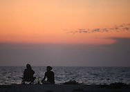 A couple enjoys the sunset on a Sanibel Island beach in Florida.