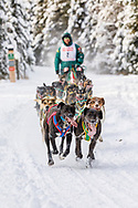 Musher Blayne Streeper competing in the Fur Rendezvous World Sled Dog Championships at Goose Lake Park in Anchorage in Southcentral Alaska. Winter. Afternoon.