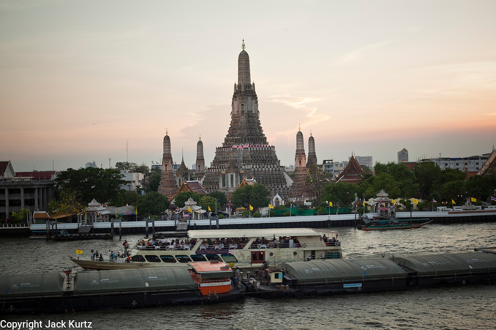 """07 MARCH 2009 -- BANGKOK, THAILAND: Sunset at Wat Arun, a Buddhist temple (wat) in the Bangkok Yai district of Bangkok, Thailand, on the west bank of the Chao Phraya River. The full name of the temple is Wat Arunratchawararam Ratchaworamahavihara. The outstanding feature of Wat Arun is its central prang (Khmer-style tower). It may be named """"Temple of the Dawn"""" because the first light of morning reflects off the surface of the temple with a pearly iridescence. Steep steps lead to the two terraces. The height is reported by different sources as between 66,80 m and 86 m. The corners are surrounded by 4 smaller satellite prangs. The prangs are decorated by seashells and bits of porcelain which had previously been used as ballast by boats coming to Bangkok from China. The central prang is topped with a seven-pronged trident, referred to by many sources as the """"trident of Shiva"""". Around the base of the prangs are various figures of ancient Chinese soldiers and animals. Over the second terrace are four statues of the Hindu god Indra riding on Erawan. The temple was built in the days of Thailand's ancient capital of Ayutthaya and originally known as Wat Makok (The Olive Temple). In the ensuing era when Thonburi was capital, King Taksin changed the name to Wat Chaeng. The later King Rama II. changed the name to Wat Arunratchatharam. He restored the temple and enlarged the central prang. The work was finished by King Rama III. King Rama IV gave the temple the present name Wat Arunratchawararam. As a sign of changing times, Wat Arun officially ordained its first westerner, an American, in 2005. The central prang symbolizes Mount Meru of the Indian cosmology. The satellite prangs are devoted to the wind god Phra Phai. Photo By Jack Kurtz / ZUMA Press"""