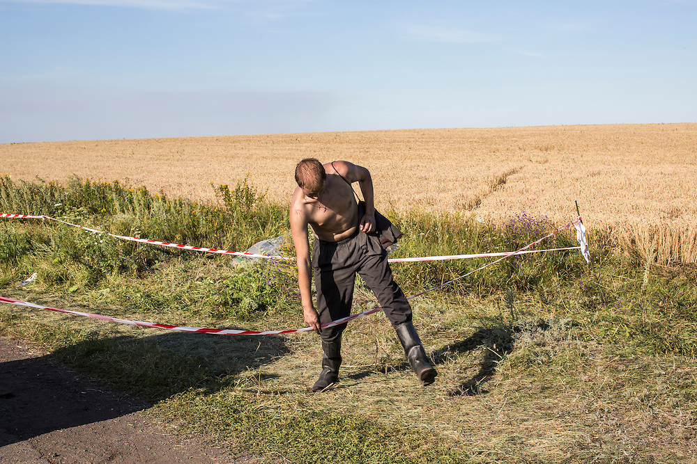 GRABOVO, UKRAINE - JULY 20: A coal miner working to sweep through the fields searching for remnants of Malaysia Airlines flight MH17 leaves the scene of the crash on July 20, 2014 in Grabovo, Ukraine. Malaysia Airlines flight MH17 was travelling from Amsterdam to Kuala Lumpur when it crashed killing all 298 on board including 80 children. The aircraft was allegedly shot down by a missile and investigations continue over the perpetrators of the attack. (Photo by Brendan Hoffman/Getty Images) *** Local Caption ***
