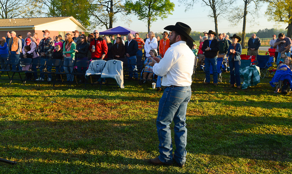 Gary Cosby Jr./Decatur Daily   Worshippers join together for a sunrise service at the No Fences Cowboy Church Easter Sunday morning in Falkville.  Pastor Josh Sparkman sings with the gathered worshippers.