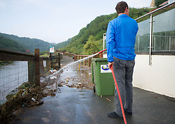© Licensed to London News Pictures. 07/09/2013<br /> <br /> Saltburn, Cleveland, England<br /> <br /> Boyd Camfield owner of Camfield's Espresso Bar hoses away rubbish from outside his cafe following an evening of torrential rainfall that caused flooding and disruption to Saltburn in Cleveland.<br /> <br /> Photo credit : Ian Forsyth/LNP