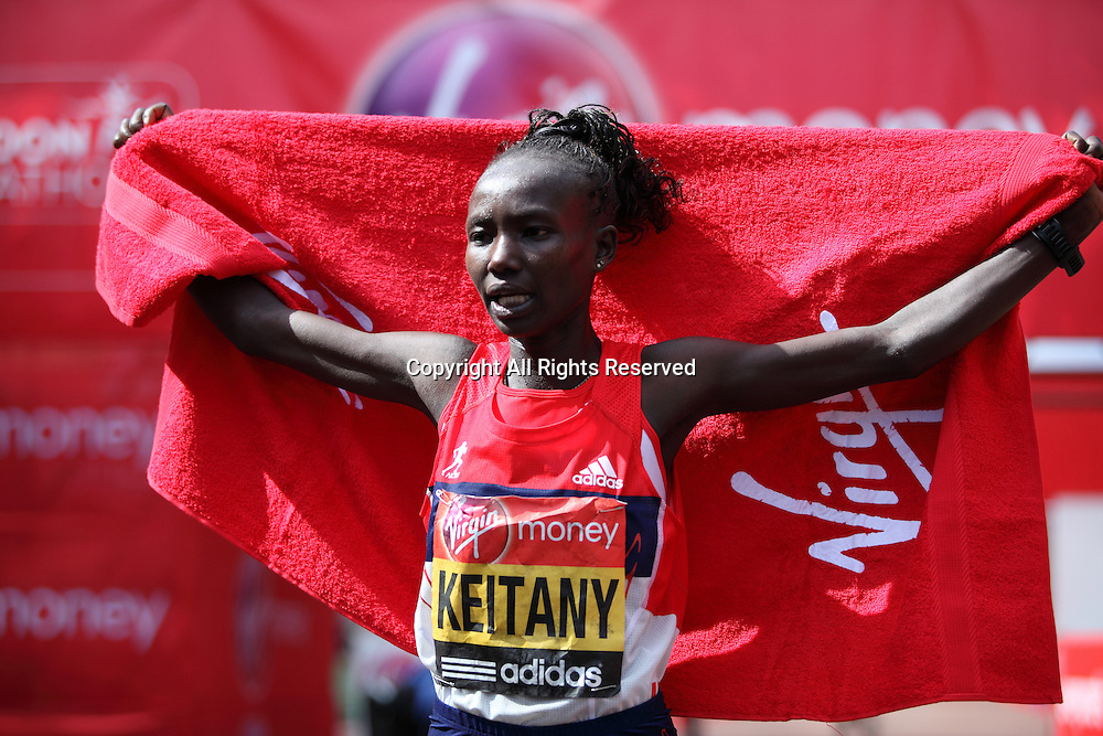 22.04.2012 London, England. The Mall, in front of Buckingham Palace. Mary Keitany (Kenya)wrapped in her national team flag wins the Womens race at The Virgin London Marathon in a time of 2:18:36