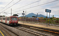 A train enters station at pompeii, Italy with Mt. Vesuvius in the background.