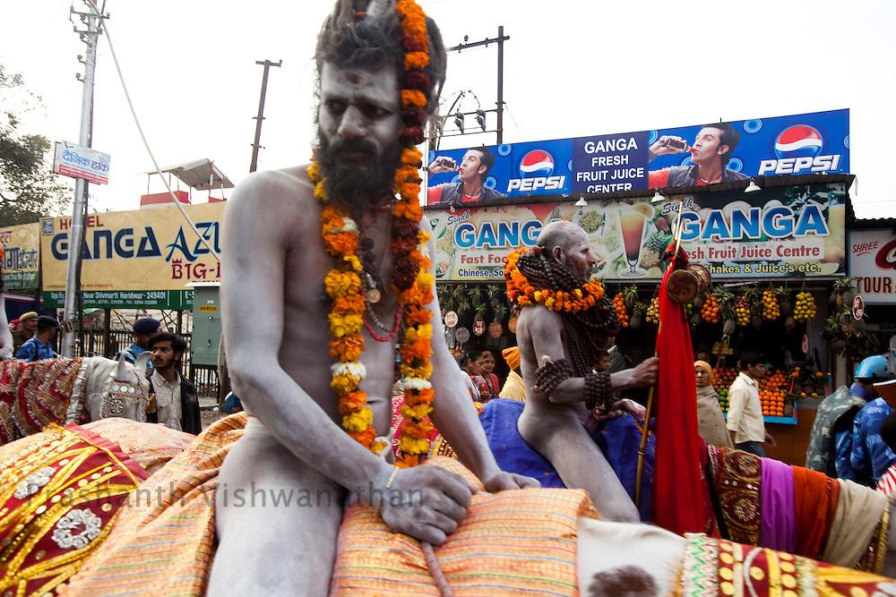 Naked Naga sadhu's walk through he streets with modern signages during he Maha Kumbh ceremony in Haridwar, February 10, 2010.  Photographer:Prashanth Vishwanathan
