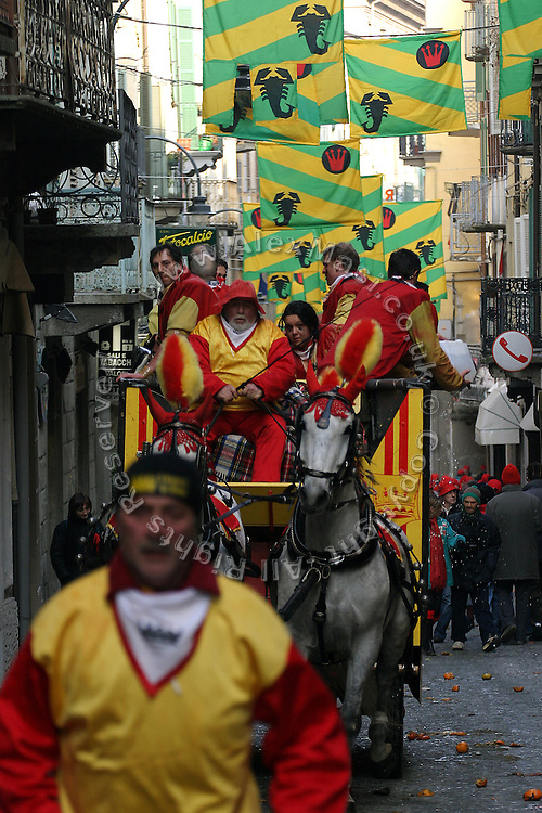 Men are running along the horse-vans through the narrow streets of Ivrea, pop. 30.000. During the days of the Carnival, the town becomes crammed with tourists coming to witness the event which finds its roots at the end of the XII Century, when the people led an insurrection against the local tyrant, Count Ranieri of Biandrate, who was exercising the 'jus primae noctis' rule (having the first night) on the local young brides. The battle to overthrow him is represented with a 3-day-fight between factions in which more then 400 tonnes of oranges are thrown. During the celebrations, food stalls, bands playing music, and parades are also present, giving it a typical Medieval atmosphere. ...