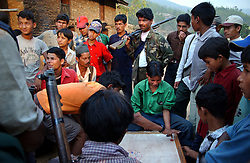 "RUKUM DISTRICT, NEPAL, APRIL 22, 2004:  Maoist insurgents play a board game in Rukum district April 22, 2004.The guerrillas' strength is hard to gauge. Analysts and diplomats estimate there about 15,000-20,000 hard-core fighters, including many women, backed by 50,000 ""militia"".  In their remote strongholds, they collect taxes and have set up civil administrations, and ""people's courts"" to settle rows. They also raise money by taxing villagers and foreign trekkers. Though young, they are fearsome fighters and  specialise in night attacks and hit-and-run raids. They are tough in Nepal's rugged terrain, full of thick forests and deep ravines and the 150,000 government soldiers are not enough to combat this growing movement that models itself after the Shining Path of Peru. (Ami Vitale/Getty Images)"