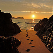 Footsteps in the sand at sunrise.<br />