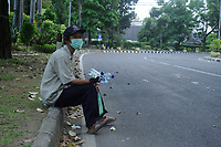 Medan, Indonesia, March 25, 2020: A water seller activity beside the silent of Medan city main roads in North Sumatra, Indonesia as humanity dailylife during warning of the spread of Corona Virus Disease (COVID) 19 in Medan, Indonesia on March 25, 2020.