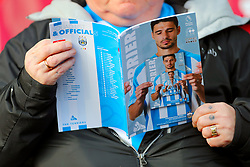 A fan reads the matchday programme ahead of the Premier League match at the John Smith's Stadium, Huddersfield.