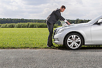 Full length side view of young businessman reading map on car hood at countryside