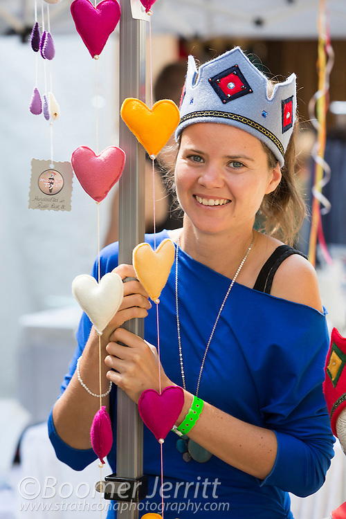 A young vendor attending the Filberg Festival wears a felt crown at her booth.  Comox, The Comox Valley, Vancouver Island, British Columbia, Canada.