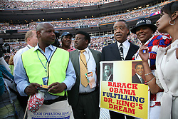 """The Reverend Al Sharpton poses for photographs with a delegate and HER sign saying """"Barack Obama Fulfilling Dr. King's Dream"""" on the delegate floor of the Democratic National Convention, Invesco Field, Denver, Colorado, August 28, 2008."""