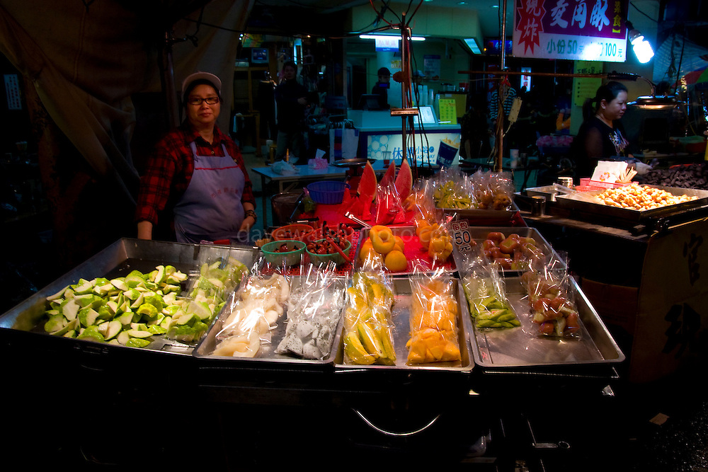 Fruit seller at the Miaokou Night Market, Keelung, Taiwan. Keelung's Miaokou Night Market is famous throughout Taiwan for its large selection of food. It meanders through lanes and alleys in the downtown area surrounding the Dianji Temple. The night market is easily accessible on foot for most travelers arriving from other cities. From the Keelung railway station walk east straight along the street following the harbor in the direction of the Keelung Harbor Bureau (identifiable at night by its large orange neon sign. The night market is roughly one block from the point where you cross a freeway overpass.