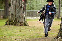 Dayton Wiksten,a first-grade student at Fernan Elementary, runs through the trees on the playground Friday during the school's Run for Fun program.