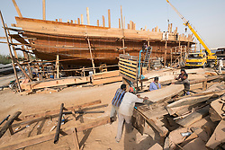 Building a traditional wooden dhow cargo ship in shipyard beside The Creek River in Dubai United Arab Emirates