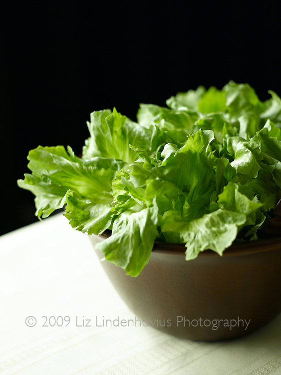 Green lettuce in wooden salad bowl