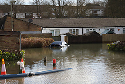 © Licensed to London News Pictures. 22/02/2014. Basingstoke, Hampshire. A car surrounded by flood water on Grampian Way, in the Buckskin area of Basingstoke, Hampshire. Groundwater levels are continuing to rise in the area, forcing 69 homes to be evacuated in the Buckskin Area of the commuter town. Photo credit : Rob Arnold/LNP
