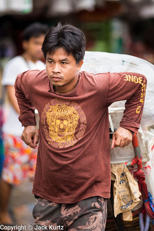 """24 AUGUST 2013 - BANGKOK, THAILAND: A porter pulls a customer's cart through Khlong Toei Market in Bangkok. Thailand entered a """"technical"""" recession this month after the economy shrank by 0.3% in the second quarter of the year. The 0.3% contraction in gross domestic product between April and June followed a previous fall of 1.7% during the first quarter of 2013. The contraction is being blamed on a drop in demand for exports, a drop in domestic demand and a loss of consumer confidence. At the same time, the value of the Thai Baht against the US Dollar has dropped significantly, from a high of about 28Baht to $1 in April to 32THB to 1USD in August.     PHOTO BY JACK KURTZ"""