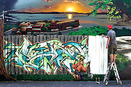 Ryan Christenson works on a mural on the back of a building at 971 Meriden-Waterbury Turnpike in Southington, CT. (Photo by Kevin Bartram)