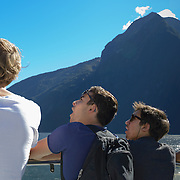 Passengers on cruise boat with blue sky at Milford Sound