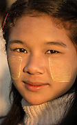 Young Burmese woman with Thanaka Root (Myanmar Face Paint ) which has numerous health benefits including: tightening of the skin, anti-septic and natural sunblock.