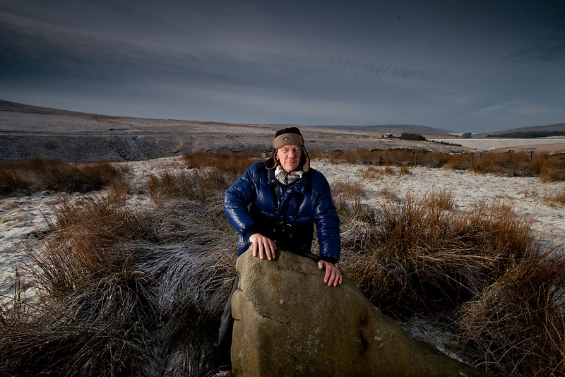 Jan 2010 Pennine Prospects PORTRAITS - Dave Shepard Archaeologist on Ridge Rough with a standing stone placed there by people of the Bronze Age aligned towards the midwinter sunrise