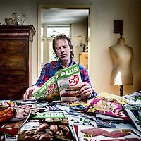 Nederland, Nunspeet, 6 mei 2016.<br /> JPJ Dick Floor uit Nunspeet verzamelt elke week voor Wakker Dier de folders van alle supermarkten en turft daarin de vleesaanbiedingen. Die zet hij in een Excel-bestand om te zien welke supermarkt het vaakst kiloknallers heeft. Zijn woonkamer wordt gedomineerd door een enorme tafel vol met folders.<br /> <br /> <br /> <br /> Foto: Jean-Pierre Jans