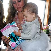 NLD/Amsterdam/20120718 - Boekpresentatie Regina Romeijn 'Vet man, zo'n baby!', Regina Romeijn met dochter Bardot die het boek van haar moeder door bladerd