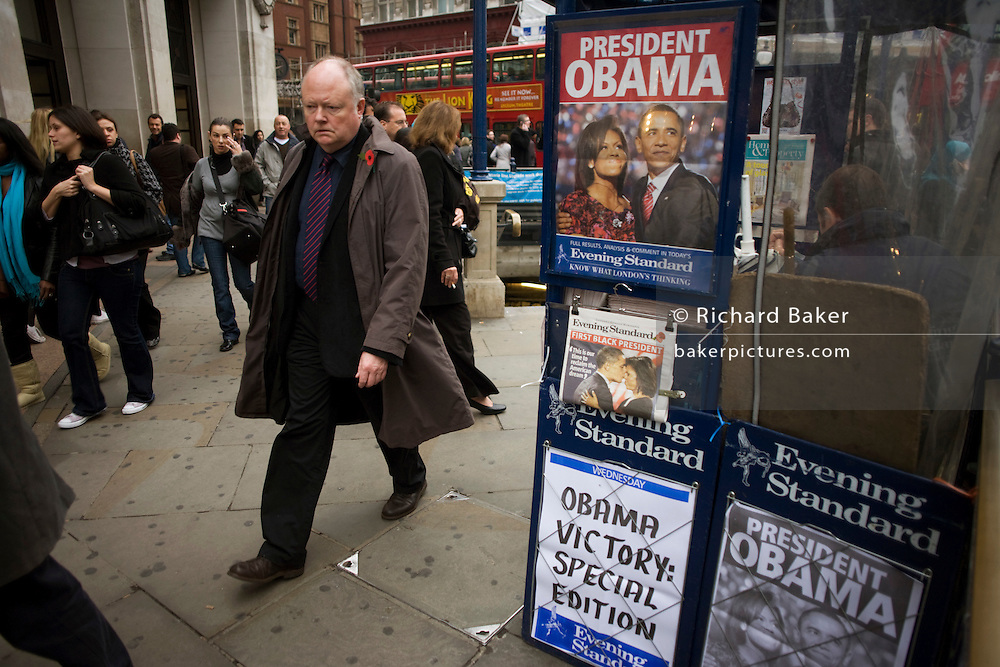 Passers-by in London's Oxford Circus take in morning news of Barack Obama's historic election victory on newspaper headlines