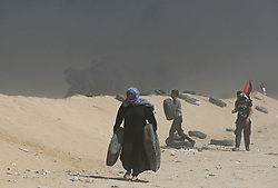 A Palestinian woman protester moves a car tyre to be burnt during clashes during clasheswith Israeli soldiers at the border fence with Israel east of Khan Yunis in the southern Gaza Strip, Israeli soldiers killed at least 60 Palestinians and wounded more than 2,700. as demonstrations on the Gaza-Israel border coincided with the controversial opening of the U.S. Embassy in Jerusalem. This marks the deadliest day of violence in Gaza since 2014. Gaza's Hamas rulers have vowed that the marches will continue until the decade-old Israeli blockade of the territory is lifted. Gaza Strip, Palestine, May 15, 2018. Photo by Ashraf Amra/SalamPix/ABACAPRESS.COM