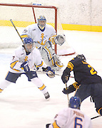Lake Superiior State University Lakers goaltender Brian Mahoney-Wilson stands ready while defender Matt Cowle (#7 white) tries to block a charge by the Casinius Griffins Carl Hudson (2 blue) during the first period of the Saturday night game.