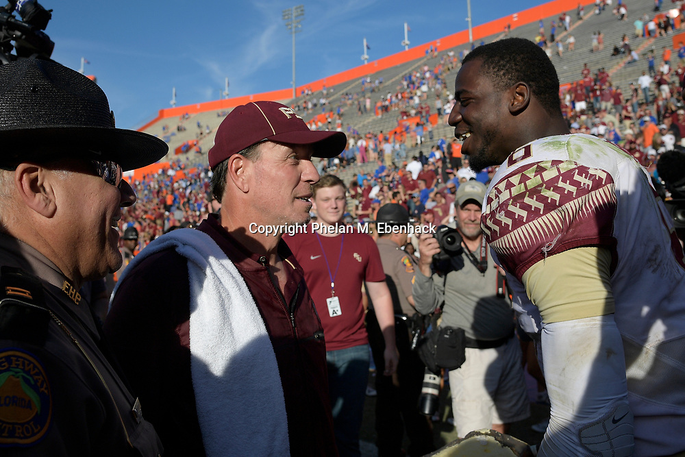 Florida State head coach Jimbo Fisher talks with linebacker Matthew Thomas (6) on the field after an NCAA college football game against Florida Saturday, Nov. 25, 2017, in Gainesville, Fla. FSU won 38-22. (Photo by Phelan M. Ebenhack)