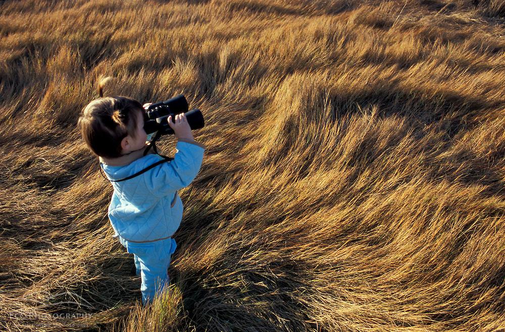 Biddeford, ME. A young girl plays with binoculars on a salt marsh near Biddeford Pool.  TPL project - Anuszewski property.