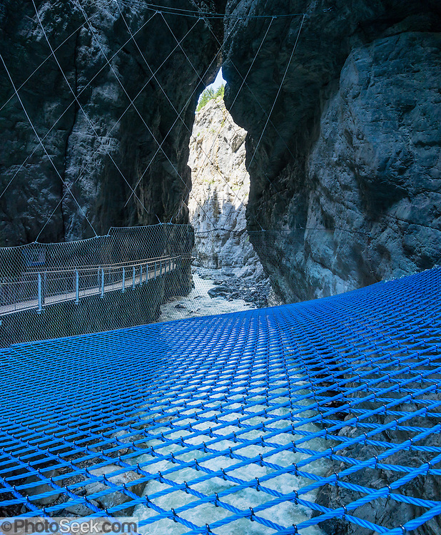 Walk across a blue net suspended over the White Lütschine river gorge, in the Gletscherschlucht of Grindelwald, Switzerland, Europe. Walk boardwalks and tunnels through the dramatic Gletscherschlucht, a deep gorge of the White Lütschine river, flowing from Lower Grindelwald Glacier. From Gletscherschlucht hotel restaurant in Grindelwald, a wooden walkway leads over raging water, through galleries and rocky tunnels over 1000 meters into the ravine, under 100-meter high cliffs. Visitors can amble on a blue net over the foaming torrent. Walk there in 35 minutes from the center of Grindelwald, or take the bus. This image was stitched from multiple overlapping photos.