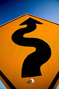 Curves ahead road sign with blue sky