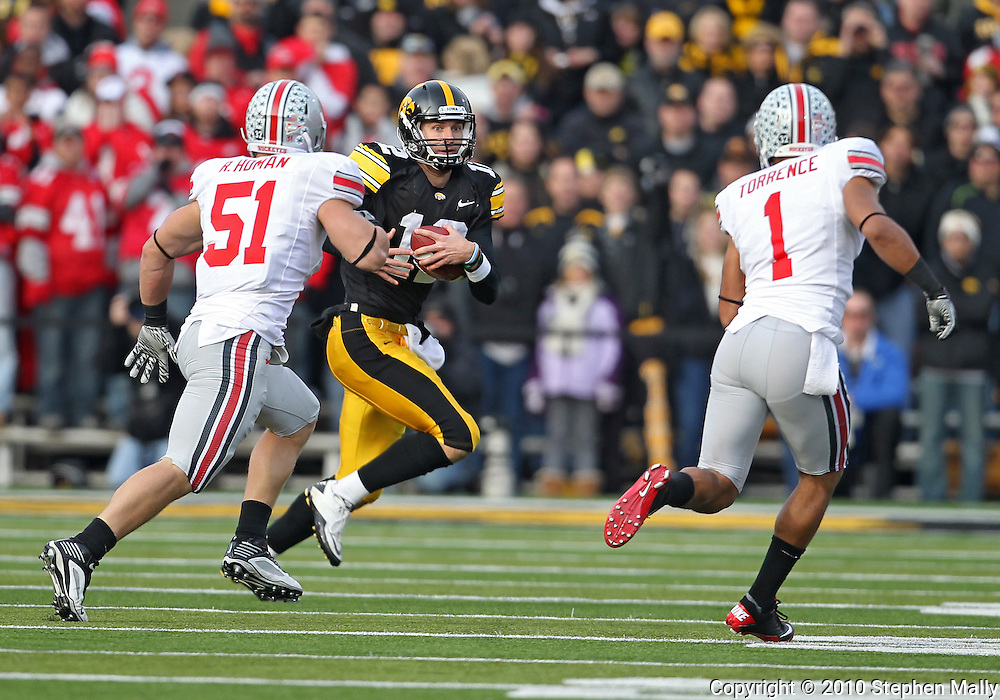 November 20 2010: Iowa Hawkeyes quarterback Ricky Stanzi (12) tries to avoid Ohio State Buckeyes linebacker Ross Homan (51) and Ohio State Buckeyes defensive back Devon Torrence (1) during the first quarter of the NCAA football game between the Ohio State Buckeyes and the Iowa Hawkeyes at Kinnick Stadium in Iowa City, Iowa on Saturday November 20, 2010. Ohio State defeated Iowa 20-17.