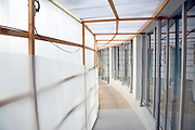hall under construction with temporary walls for people to walk